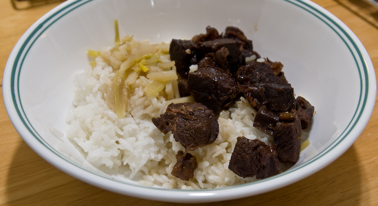 Beef cooked in soy sauce with celery and potatoes over rice
