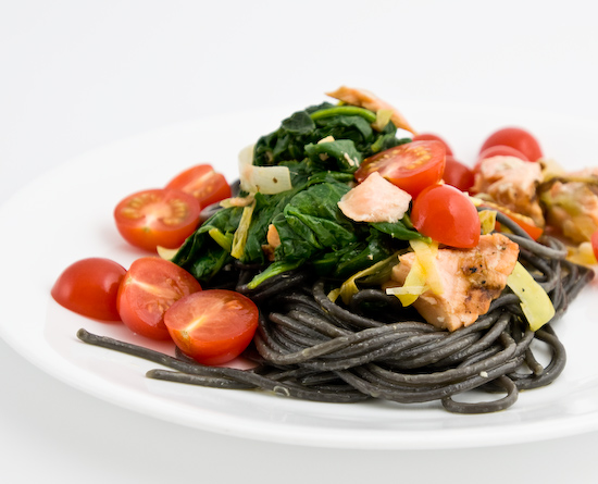 Squid ink spaghetti tossed in olive oil, garlic, and leeks topped with reheated left over salmon and spinach with fresh cherry tomatoes
