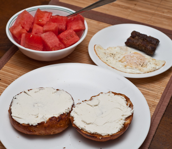 Cinnamon Crunch Bagel with Cream Cheese, an Egg Over Easy, Breakfast Sausages, and Watermelon