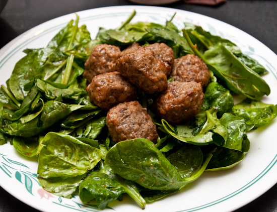 Aidell's meatballs on a wilted spinach salad