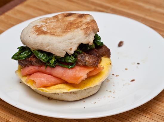 Egg, smoked salmon, breakfast sausage, arugula, and English muffin sandwich